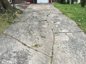 A severely cracked concrete driveway requires replacement