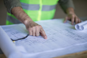 man in neon vest pointing to blueprint