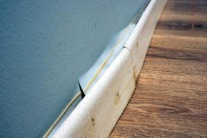 split wallpaper on displaced baseboard