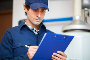 man in blue hat writing on a clipboard