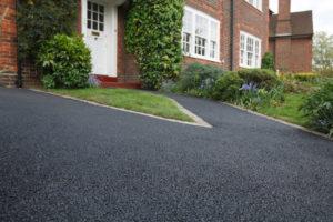asphalt driveway outside brick house