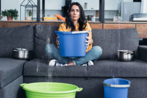 woman sitting on couch holding bucket under leak