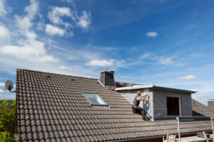 View of a rooftop with a working roofer