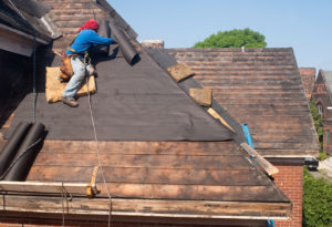 roofer laying underlayer on roof