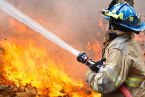 firefighter spraying water on blaze